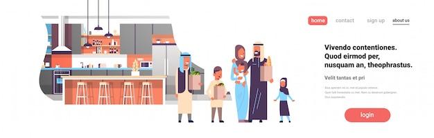 Arabische familie, die taschen mit lebensmittelgeschäftprodukten in der küchenfahne hält