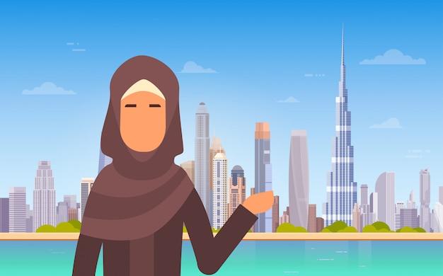 Arabische frau, die dubai-skyline-panorama, moderne gebäude-stadtbild-geschäftsreise und tourismus-betrug zeigt