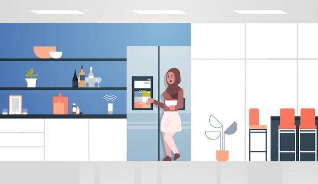 Arabische frau, die kühlschrankbildschirm mit intelligenter sprecherstimme berührt