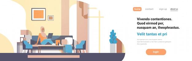 Arabische frau, die laptopwohnzimmerinnenhauptmoderne wohnung verwendet