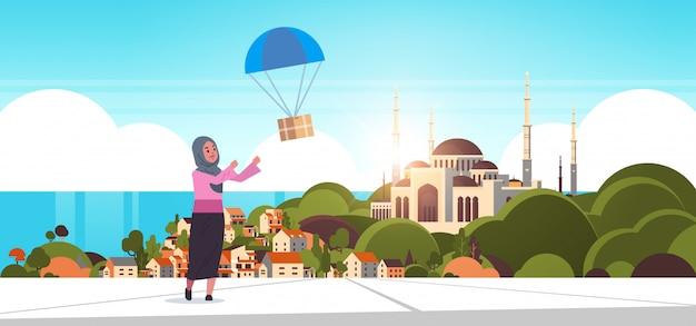 Arabische frau, die paketbox fängt, die mit fallschirmversandpaket luftpost expresspostversandkonzept nabawi moschee gebäude muslimischen stadtbildhintergrund in voller länge horizontal herunterfällt