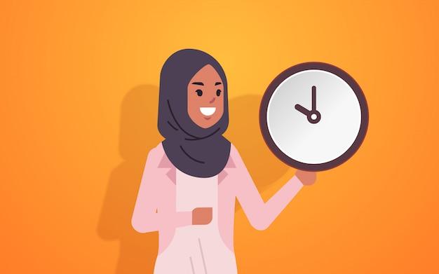 Arabische frau, die uhrzeitmanagement-fristkonzept arabische geschäftsfrau mit weckerin weibliches zeichentrickfigurporträt horizontal hält