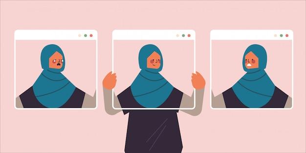 Arabische frau, die webbrowserfenster mit verschiedenen maskenmädchen hält, die gesichtsgefühle abdecken gefälschtes gefühl depression geistesstörung konzept porträt horizontale illustration