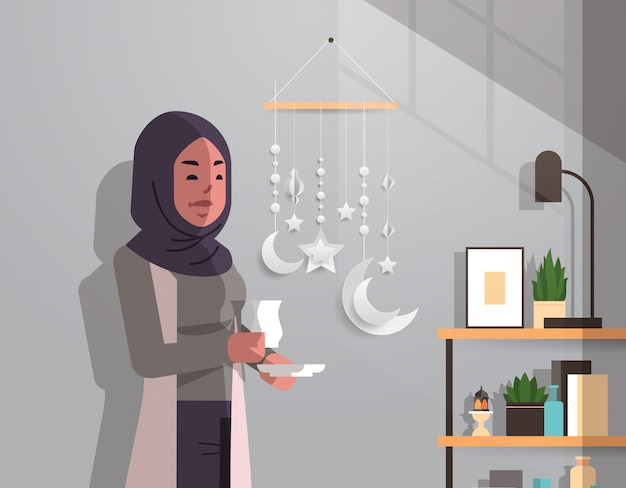 Arabische frau in traditioneller kleidung, die kaffee trinkt, der das moderne vertikale porträt des modernen wohnzimmers des ramadan kareem heiligen monats feiert