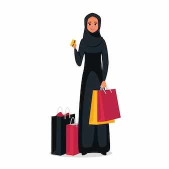 Arabische frau mit den bunten einkaufstaschen, die eine kreditplastikkarte halten. vektor