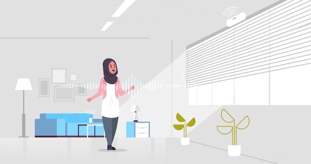 Arabische frau unter verwendung der spracherkennung der intelligenten sprecher-aktivierten digitalen assistentenkonzept
