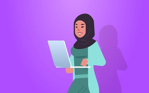 Arabische geschäftsfrau, die an laptop arabischer frau büroangestellter in der formellen abnutzung unter verwendung der computeranwendungsporträt horizontal arbeitet