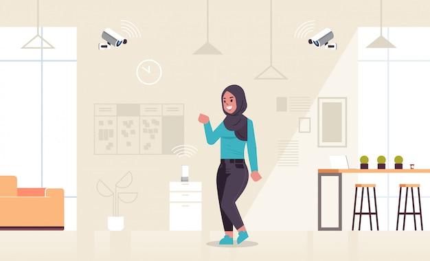 Arabische geschäftsfrau mit cctv-kamera gesteuert