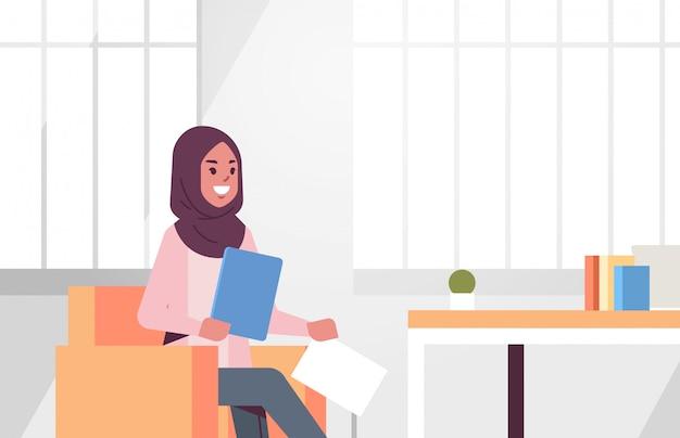 Arabische geschäftsfrau sitzt am arbeitsplatz schreibtisch arabische geschäftsfrau hält papier dokumente vorbereitung bericht arbeitsprozess moderne büroeinrichtung