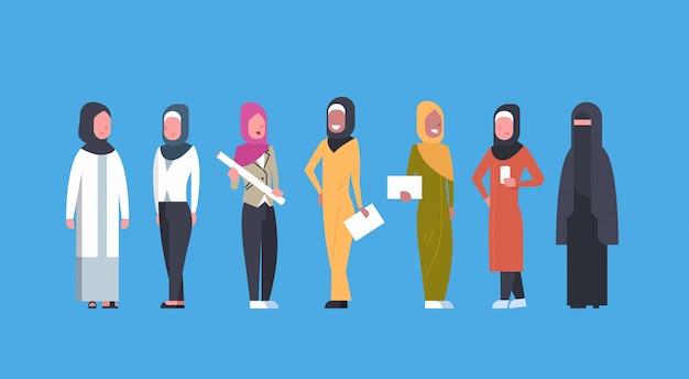 Arabische geschäftsfrauen gruppieren die arabischen geschäftsfrauen in voller länge, die traditionelle kleidung, moslemische weibliche menge tragen