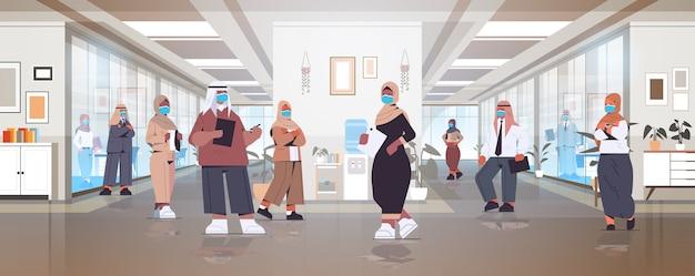 Arabische geschäftsleute in schutzmasken, die abstand halten, um zu verhindern, dass arabische kollegen der coronavirus-pandemie in voller länge im büroflur stehen