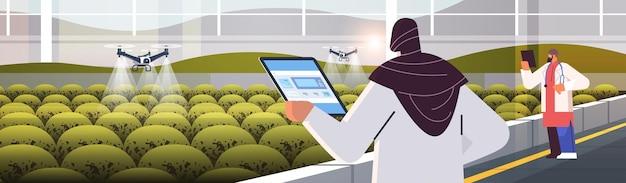 Arabische ingenieure, die landwirtschaftliche drohnen-sprühgeräte quad-copter kontrollieren, die fliegen, um chemische düngemittel im gewächshaus zu sprühen smart farming innovation technologiekonzept horizontale vektorillustration