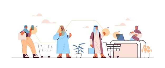 Arabische kunden, die smartphones zum bezahlen an der kasse beim online-shopping verwenden