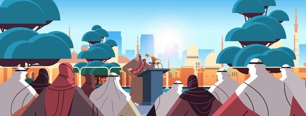 Arabischer bürgermeister mit schlüsselrede vom horizontalen stadtbildhintergrund der tribüne