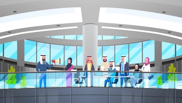 Arabischer geschäftsmann-boss hold megaphone make-mitteilungs-kollege-islam-geschäftsleute team group meeting im modernen büro