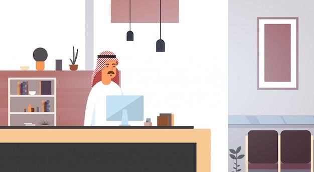 Arabischer geschäftsmann, der computer-moslemischen unternehmer im modernen büro verwendet