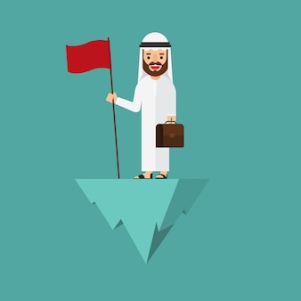 Arabischer geschäftsmann, der mit flagge auf den hügel steht