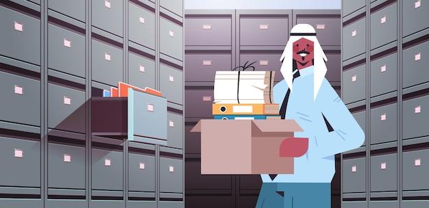 Arabischer geschäftsmann, der pappkarton mit dokumenten im aktenwandschrank mit offener schublade datenarchivspeicher business administration papierarbeitskonzept horizontale porträtvektorillustration hält