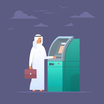 Arabischer mann, der atm-maschine nimmt geld von der kreditkarte, islam-geschäftsmann wearing traditional clot verwendet