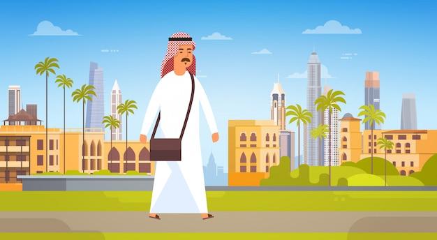 Arabischer mann, der moderne stadt-gebäude-stadtbild-skyline-panorama-geschäftsreise und tourismus-konzept geht