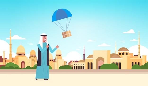 Arabischer mann, der paketbox fängt, der mit fallschirmversandpaket luftpost expresspostversandkonzept nabawi moschee gebäude muslimischen stadtbildhintergrund in voller länge horizontal herunterfällt