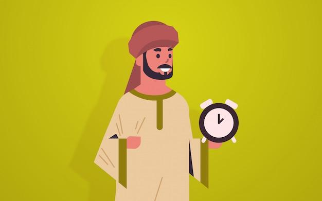 Arabischer mann, der uhrzeitmanagement-fristkonzept hält arabischer geschäftsmann mit wecker männlicher zeichentrickfigur porträt horizontal