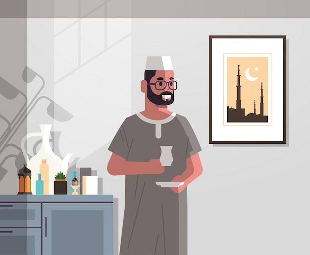 Arabischer mann in der traditionellen kleidung, die kaffee trinkt, der das moderne vertikale porträt des modernen wohnzimmers des ramadan kareem heiligen monats feiert