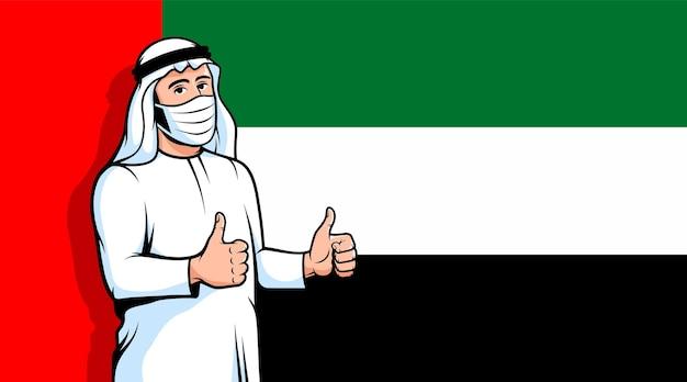 Arabischer mann in medizinischer maske daumen hoch auf flagge der vereinigten arabischen emirate hintergrund neue normalität