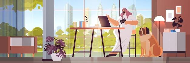 Arabischer mann mit kreditkarte mit laptop-online-shopping-konzept wohnzimmer interieur horizontal