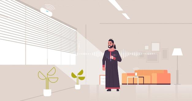 Arabischer mann mit smart speaker spracherkennung aktiviert digitalen assistenten