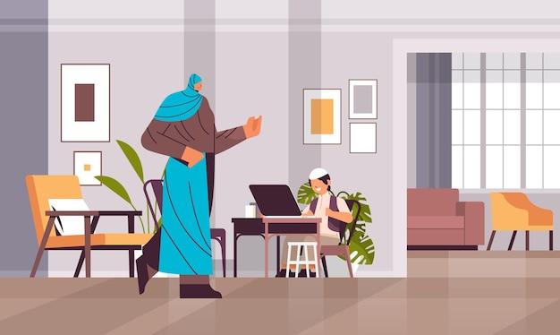Arabischer schuljunge mit laptop kleiner arabischer junge mit mutter, die hausaufgabenbildungskonzept wohnzimmerinnenraum macht