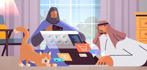 Arabisches paar mit kreditkarte mit laptop-online-shopping-konzept mann frau, die zusammen waren bestellt
