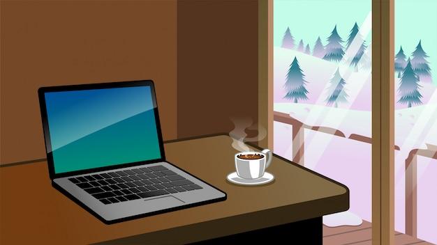 Arbeitsschreibtisch mit laptop und kaffee neben der naturwinter-landschaftsansicht