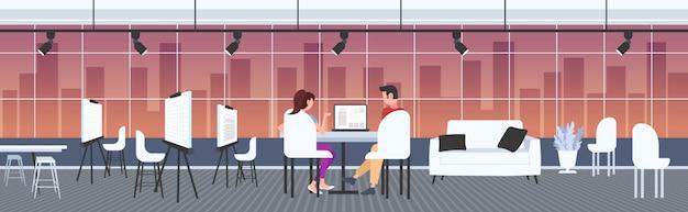 Architektenpaar mit laptop-ingenieuren, die ein hausprojekt auf einem computerbildschirm mit bauplänen für bauunternehmer entwerfen, die einen modernen zeichner-studio-innenraum in voller länge horizontal gestalten