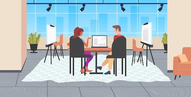 Architektenpaar mit laptop-ingenieuren, die ein hausprojekt auf einem computerbildschirm mit bauplänen für bauunternehmer entwerfen, die einen modernen zeichner-studio-innenraum in voller länge planen