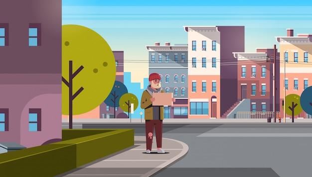 Armer bärtiger mann, der um hilfe bettelt bettler kerl hält schild obdachlos arbeitslos moderne stadtstraße stadtbild