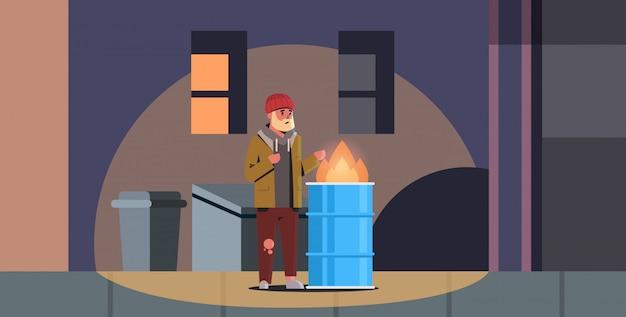 Armer bärtiger mann wärmt seine hände durch feuer bettler kerl in der nähe von brennendem müll in fass obdachlosen arbeitslosen mülleimer stadt nacht straße