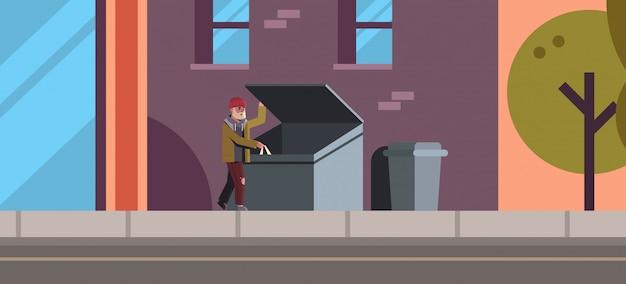 Armer mann auf der suche nach essen und kleidung im mülleimer im freien obdachlose arbeitslose stadtstraße gebäude außen