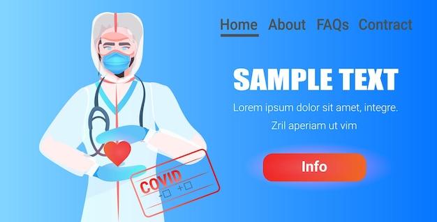 Arzt in maske und schutzanzug hält rotes herz kampf gegen covid-19 konzept porträt horizontal
