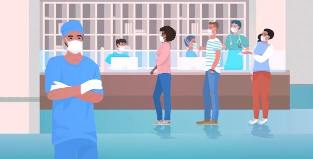 Arzt- und mischrassenpatienten, die gesichtsmasken tragen, um die schwesternstation des coronavirus-pandemiekrankenhauses zu verhindern
