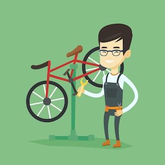 Asiatischer fahrradmechaniker, der in der reparaturwerkstatt arbeitet.
