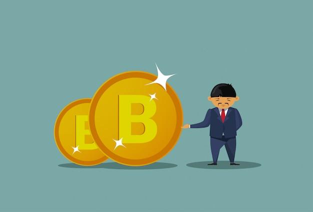 Asiatischer geschäftsmann, der bitcoins-münzen hält