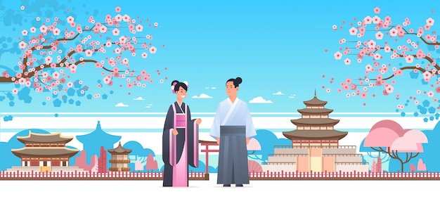 Asiatisches paar, das traditionelle kleidungsmannfrau im alten kostüm trägt, das zusammen chinesische oder japanische zeichen über pagodengebäudelandschaft steht