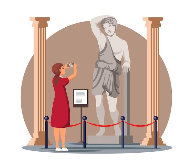 Aufgeregte frau, die antike statue im historischen museum fotografiert