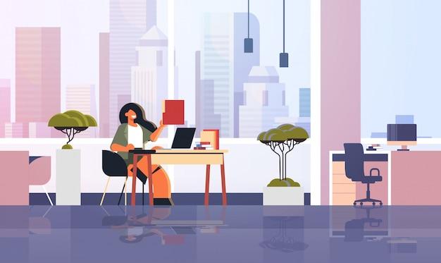 Aufgeregte geschäftsfrau, die papierdokumentordner-geschäftsfrau-sekretärin hält, die am arbeitsplatz mit modernem büroinnenraum des laptops in voller länge horizontal sitzt