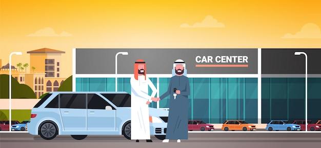 Auto-ausstellungsraum-hintergrund, kauf-verkauf oder mietzentrum-arabischer verkäufer-mann, der dem inhaber schlüssel gibt