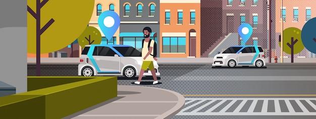 Autos mit standort pin auf der straße online bestellen taxi carsharing konzept mobilen transport mann mit carsharing-service moderne stadt straße stadtbild hintergrund horizontal