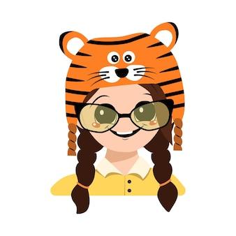 Avatar eines mädchens mit großen augen, brille und breitem, glücklichem lächeln im tigerhut. nettes kind mit fröhlichem gesicht im festlichen kostüm für neujahr, weihnachten und urlaub. kopf eines entzückenden kindes mit glücklichen emotionen