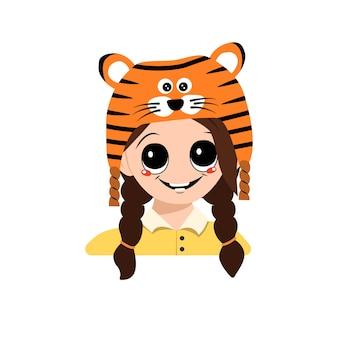 Avatar eines mädchens mit großen augen und einem breiten lächeln in einem tigerhut. nettes kind mit einem fröhlichen gesicht in einem festlichen kostüm für neujahr, weihnachten und urlaub. kopf eines entzückenden kindes mit glücklichen emotionen