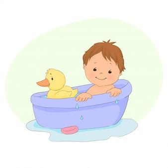 Baby, das ein bad nimmt und mit gelber gummiente spielt